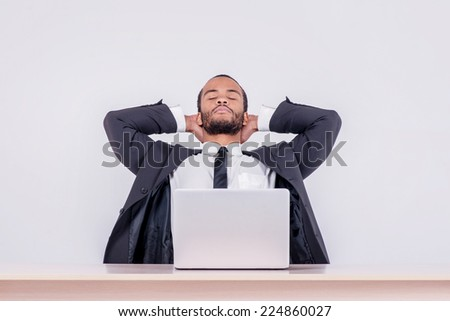 Relaxing at work. Smiling African businessman sitting at a desk on a laptop while a businessman sitting at a table and  holding his hands behind his head on isolated gray background - stock photo