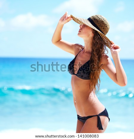 Relaxing beach woman enjoying the summer sun happy with hat - stock photo