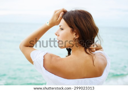 Relaxing beach woman enjoying the summer sun in white dress. Glamorous girl with gold tattoo on the hand. - stock photo