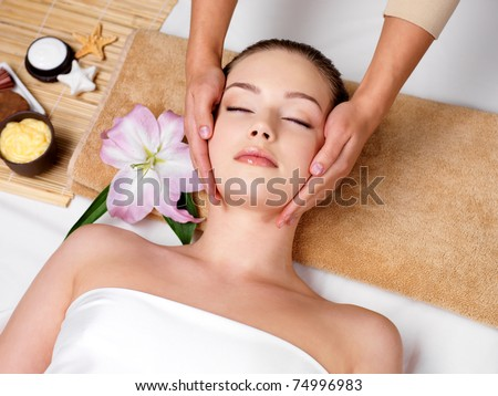 Relaxing beautiful woman having a massage for her skin on a face in beauty salon - horizontal - stock photo