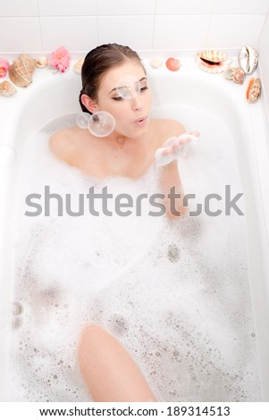 relaxing beautiful woman lying in a spa bath with foam and shell  having fun blowing soap bubbles portrait - stock photo