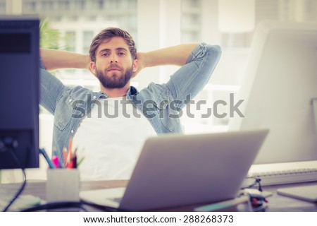 Relaxing businessman lying in chair in the office - stock photo