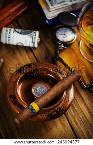 Relaxing cuban cigar after hard day, with glass of Rum - stock photo