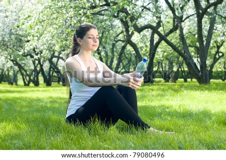 Relaxing girl with bottle of water - stock photo