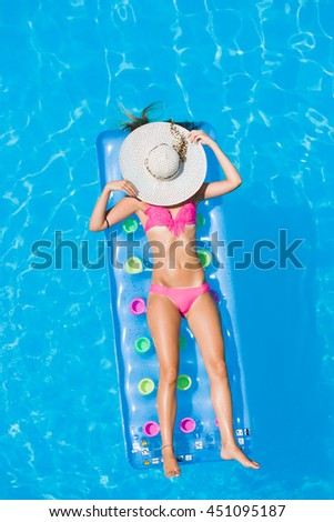 Relaxing in a swimming pool on an air mattress - stock photo