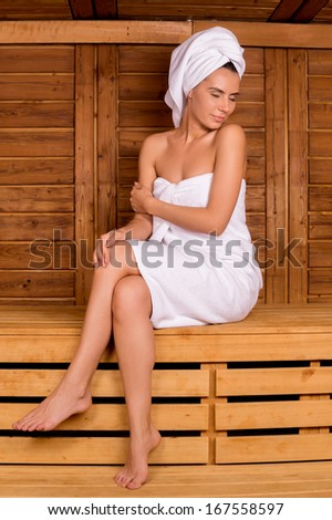 Relaxing in sauna. Attractive young woman wrapped in towel spending time in sauna and keeping eyes closed - stock photo