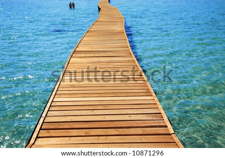 relaxing in the red sea. Idyllic seascape with pier and silhouette of two people - stock photo