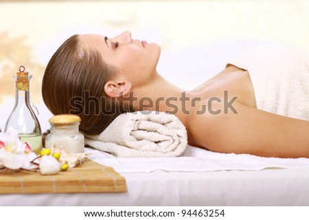 Relaxing massage for young beautiful woman in the spa salon - stock photo