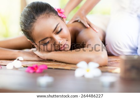 Relaxing massage of back for young beautiful woman in spa salon - stock photo