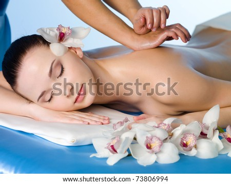Relaxing massage of back for young beautiful woman in spa salon - horizontal - stock photo