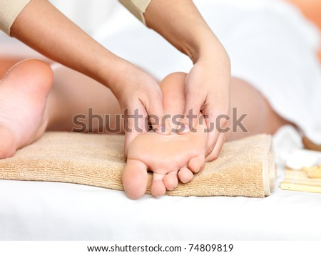 Relaxing massage on the foot  in spa salon - indoors - stock photo