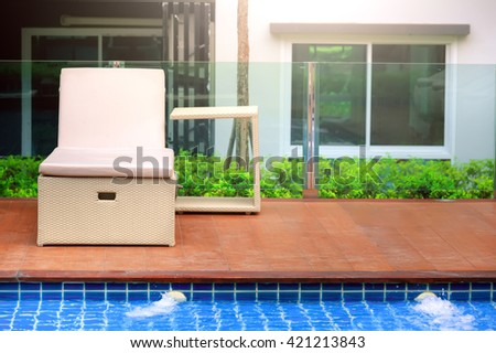 Relaxing pool bed beside swimming pool - stock photo