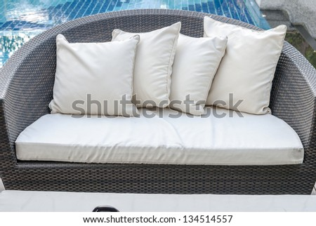 Relaxing seat sofa with pillows beside swimming pool. - Outside Interior - stock photo