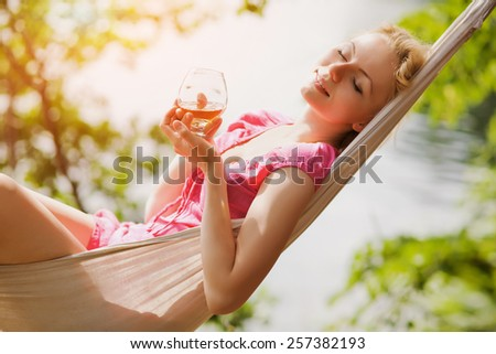 relaxing sexy woman lying in a hammock with a glass in her hands outdoors - stock photo