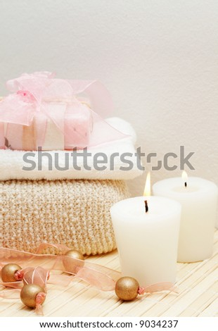 Relaxing spa scene with exfoliating sponge, face towel and handmade soap with candles - stock photo