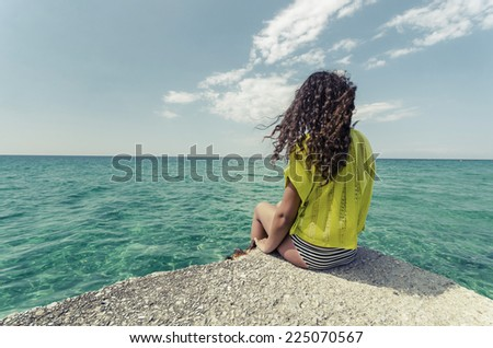 Relaxing teenage girl. Curly hair young woman is enjoy calm ocean water surface and clear sky and horizon at bahamas. - stock photo