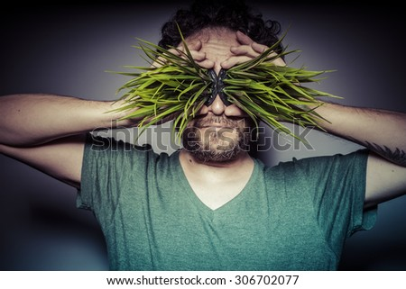 Relaxing, vegetarian concept, man with green grass in the mouth - stock photo
