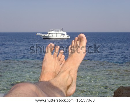 relaxing view of boat after feet from coral shore - stock photo