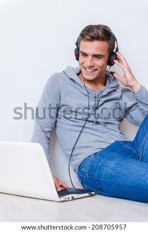Relaxing with her favorite music. Happy young man in headphones listening to the music and looking at laptop while sitting on the floor with laptop near him  - stock photo
