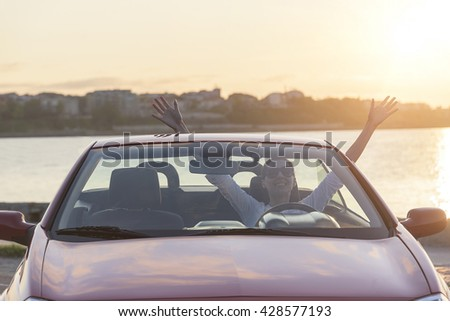 Relaxing woman on the beach in the car at sunset. Vacation or travel concept. - stock photo