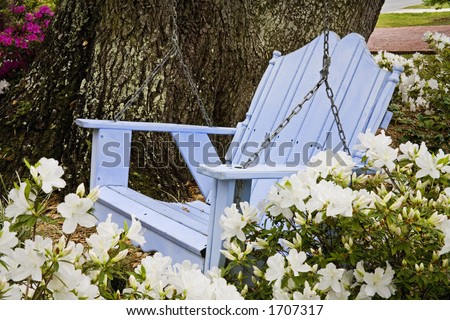 Relaxing wooden blue swing with azaleas in the Southern USA - stock photo