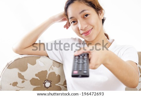Relaxing young asian girl holding a television remote control. - stock photo