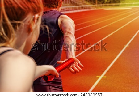 Relay race handing over from woman to man - stock photo