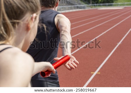 Relay race handing over from woman to man. Unfiltered version - stock photo