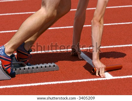 Relay runner in starting blocks ready for the start with baton in hand - stock photo