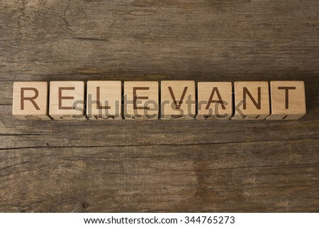 RELEVANT text on a wooden background - stock photo