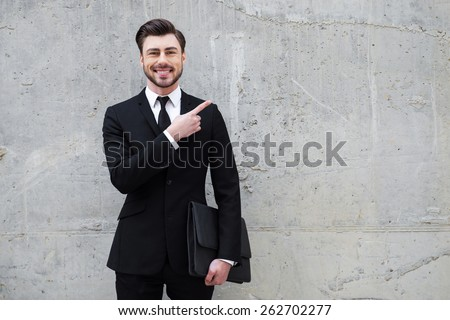 Reliable expert. Handsome young man holding briefcase while standing outdoors and against the concrete wall - stock photo