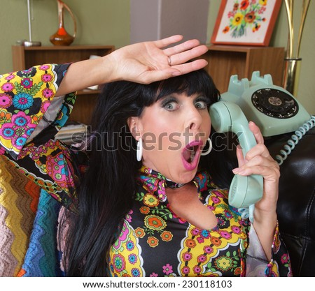 Relieved woman in paisley on rotary telephone - stock photo