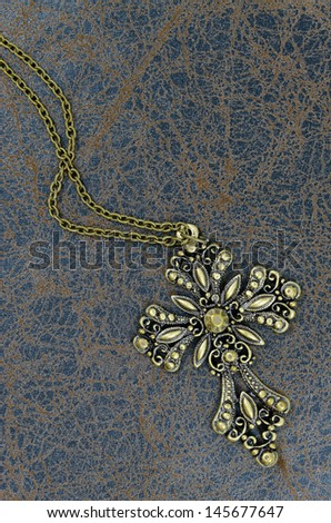 Religion. A cross with a chain against a old book - stock photo