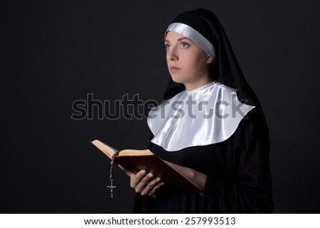religion concept - young beautiful woman nun reading bible over grey background - stock photo