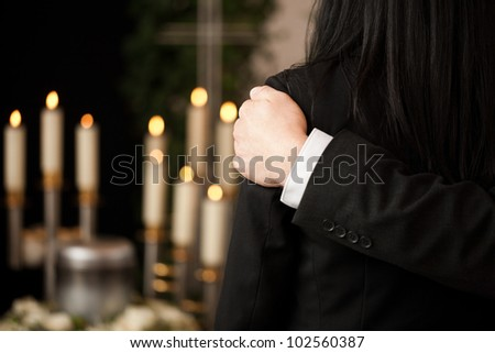 Religion, death and dolor  - couple at funeral consoling each other in view of the loss - stock photo