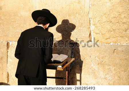 Religious orthodox jew praying at the Western wall in Jerusalem old city. - stock photo