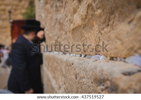 Religious orthodox jew praying at the Western Wall in the old city of Jerusalem Israel. There are notes to God in the cracks between the bricks. - stock photo