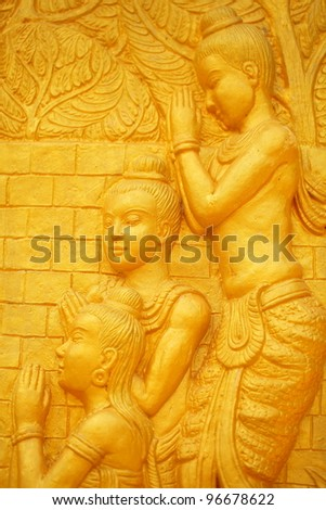 Religious statues on the wall in a Thai temple. - stock photo