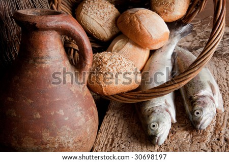 Religious still life of 5 loaves of bread, an antique wine jug and 2 fish - stock photo