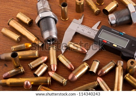 Reloading bench with cartridges and shell casings - stock photo