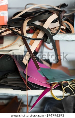 Remainders of the leather bags on shelf in workroom - stock photo