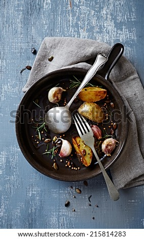 Remains of oven-baked potatoes in a ceramic dish - stock photo