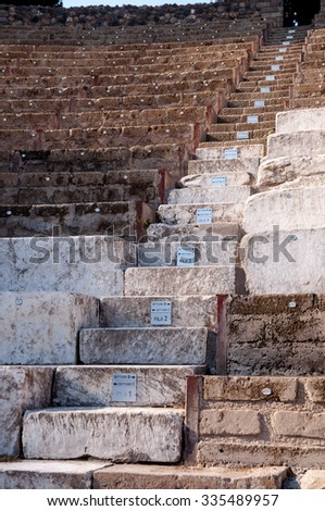 Remains of steps at large theatre in Pompeii, Italy. Pompeii was destroyed and buried with ash and pumice after Vesuvius eruption in 79 AD. - stock photo