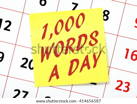 Reminder on a yellow sticky note posted on a calendar to write one thousand words a day for aspiring writers and authors - stock photo