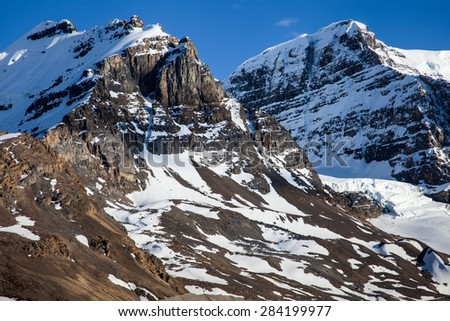 Remnants of glacier in high mountain peak - stock photo