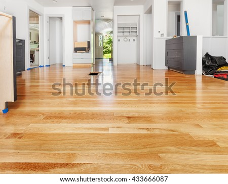 Remodeled kitchen has existing hardwood floor patched and refinished - stock photo