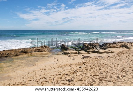 Remote beach at Penguin Island with limestone rock and Indian Ocean seascape under a blue sky with clouds in Rockingham, Western Australia/Remote Seascape/Penguin Island, Rockingham, Western Australia - stock photo