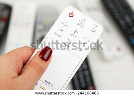 Remote control device in hand - stock photo