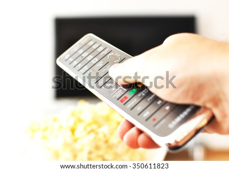 Remote control in the hand against pop-corn and TV-set - stock photo