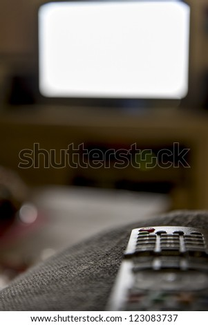 remote control with tv in the background - stock photo
